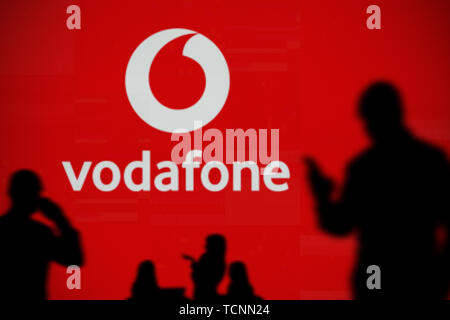 The Vodafone logo is seen on an LED screen in the background while a silhouetted person uses a smartphone in the foreground (Editorial use only) - Stock Image