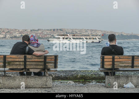 A couple share a moment of affection, and a single man reads a magazine on public benches along the Bosphorus, on - Stock Image