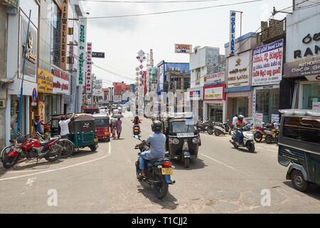 Busy commercial road in Negombo, Sri Lanka, on a sunny day, with heavy traffic of bicycles, cars, motorbikes and tuk-tuks. - Stock Image