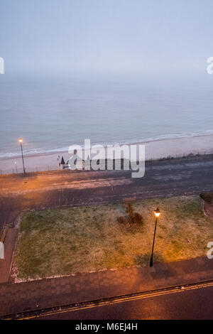 Victoria Parade, Ramsgate; walking along the seafront during a snow flurry in February. - Stock Image