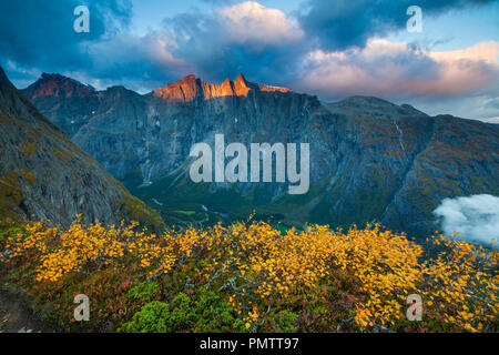 Autumn morning in Romsdalen valley, Møre og Romsdal, Norway. The sunlit mountains in the background are the 3000 feet vertical Troll Wall and the peaks Trolltindane. - Stock Image