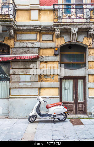 Scooter parked on pavement outside building with peeling paint, Gijon, Spai - Stock Image