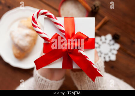 Hands of woman holding Christmas present with candy cane - Stock Image