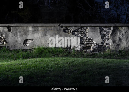 Old Stone Wall Crumbling At Night - Stock Image