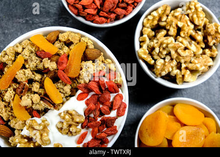 Healthy Breakfast of Cereals With Dried Fruit, Nuts and Yogurt, Apricots, Goji Berries, Granola, Almonds and Walnuts - Stock Image