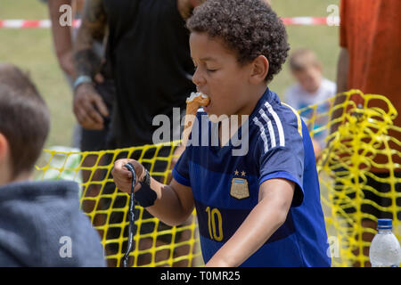 Small boy holding his ice cream cone in his mouth - Stock Image