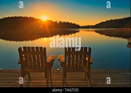 Muskoka chairs on Snake Island Lake (Cassels Lake) at sunrise Temagami Ontario Canada - Stock Image