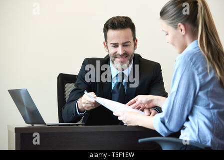 Businessman and businesswoman having meeting in office - Stock Image