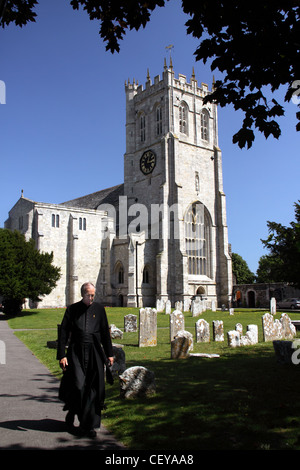 The Priory Church Parish of Christchurch, Dorset South West England with a passing priest - Stock Image