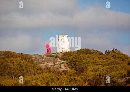 Young child in sitting by the ordnance survey trig point on top of the national trust Bosley Cloud / Cloud End near Congleton Cheshire England UK - Stock Image