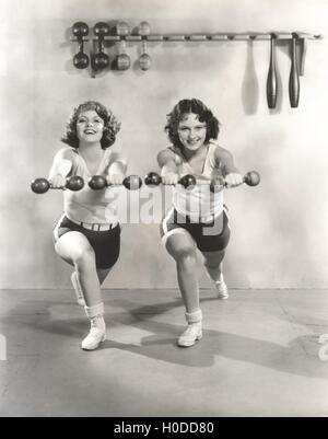 Two women exercising with dumbbells at gym - Stock Image