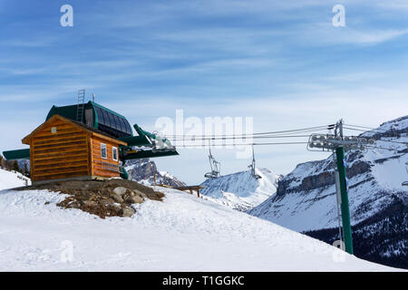 Final stop of a ski lift in the Canadian Rockies of Lake Louise with empty lift chairs. - Stock Image