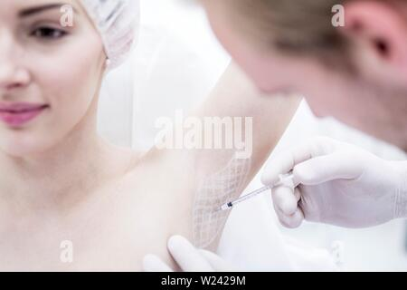 Dermatologist injecting botox in underarm to treat excessive sweating, close-up. - Stock Image