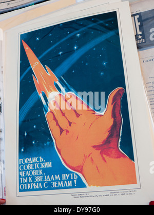 An old Russian propaganda poster promoting space race technology for sale at the flea market in Kiev Ukraine - Stock Image