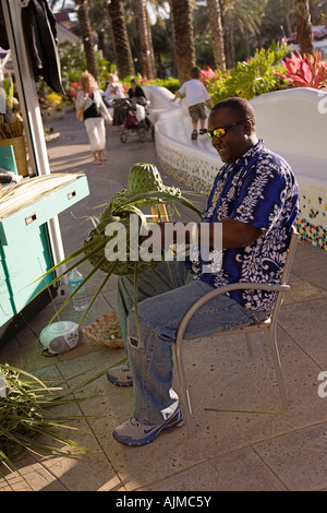 Man weaving hats out of palm fronds - Stock Image