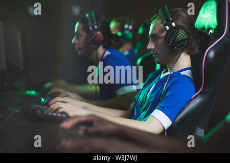 Group of concentrated video game club participants in modern headsets sitting in row and playing computer game - Stock Image