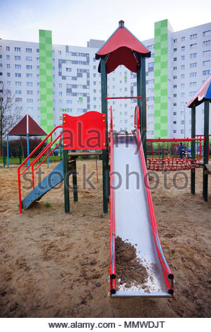 Sand at the end of a slide on a playground with apartment building on the background on the Orla Bialego district in Poznan, Poland - Stock Image