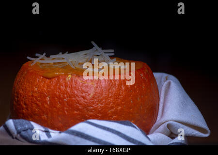 Pumpkin soup served in baked mini-pumpkin wrapped in white dish cloth against black background - seasonal dish - Stock Image