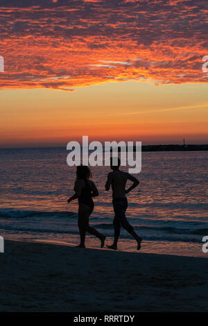 A couple running on the beach at sunset, Tayelet of Tel Aviv, Israel - Stock Image