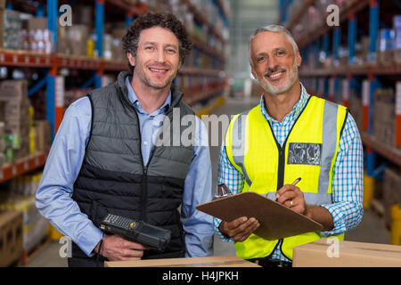 Portrait of warehouse workers standing with clipboard and barcode scanner - Stock Image