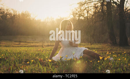 Attractive girl in white dress sits with bouquet of primroses in forest glade. She basks in sun. The concept of relaxation and inspiration. Unity with - Stock Image