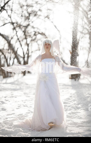 Beautiful blonde girl stands in snowy forest in image of good angel with wings dressed in white clothing against background of snowfall. - Stock Image