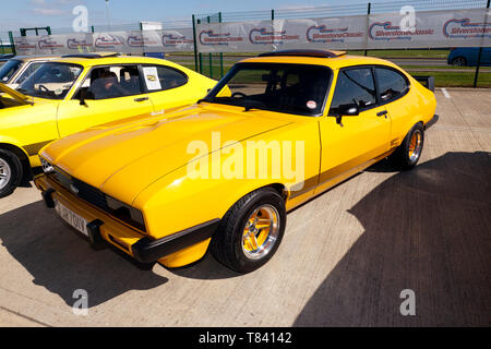 Three-quarters front view of a Yellow , Ford Capri S, part of the 50th Anniversary celebrations at the 2019 Silverstone Classic Media Day - Stock Image