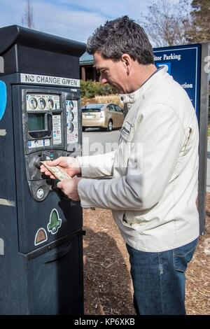 caucasian man with dark hair in his 40´s, 45´s putting cash dollar money in the car meter. - Stock Image