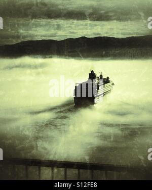Cruise ferry in the mist entering the harbour of Bergen, Norway. - Stock Image