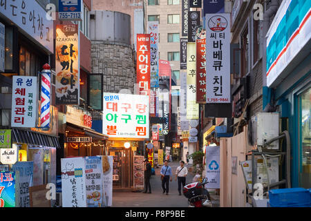 Commercial street in Seoul, South Korea, cluttered with shop signs lighting. - Stock Image