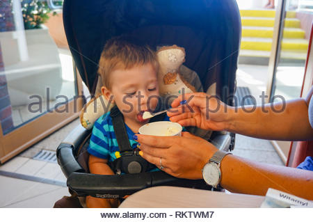 Sarbinowo, Poland - August 4, 2018: Young small toddler boy eating ice cream from a paper cup given by a adult  while sitting in a chair in the Swiat  - Stock Image