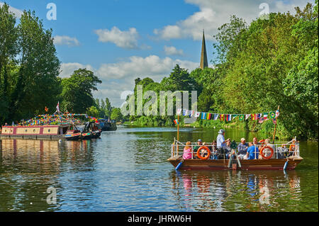 Stratford upon Avon and the old chain ferry, decked in bunting crosses the River Avon during the river festival. - Stock Image
