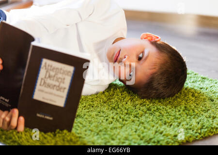 boy reading a book on ADD - Stock Image