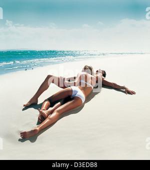 Couple lying on the beach - Stock Image