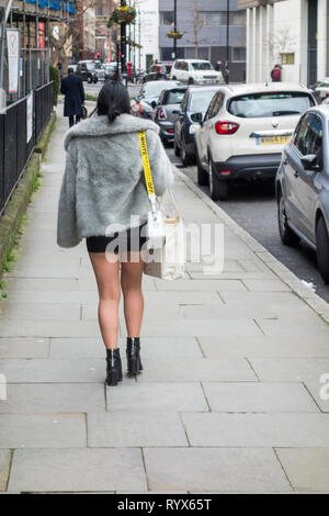 A young woman walking on a London street, UK - Stock Image