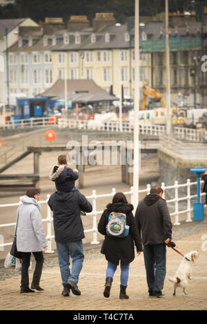 Aberystwyth Wales UK, Tuesday 16 April 2019.  UK Weather : People on the promenade on a dull and damp but mild day at the seaside in Aberystwyth Wales as the Easter school holidays get into swing. Photo credit Keith Morris / Alamy Live News - Stock Image