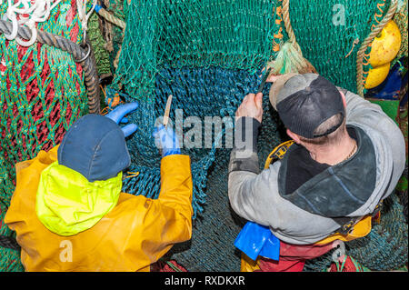 Union Hall, West Cork, Ireland. 9th March, 2019. Fishermen mend broken nets on the fishing trawler 'Ocean Pioneer' whilst moored in Union Hall Fishing Harbour. Credit: Andy Gibson/Alamy Live News. - Stock Image