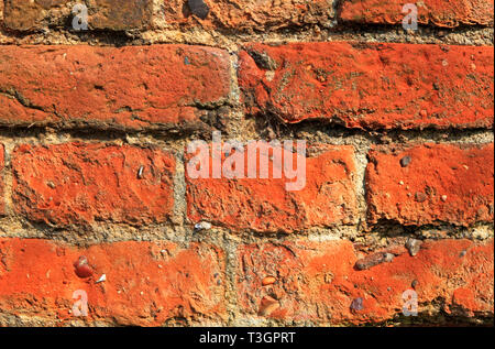 An old weathered red brick wall full of texture and pattern. - Stock Image
