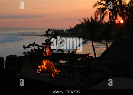 Orange sunset at a tropical beach with a small fire in El Salvador - Stock Image