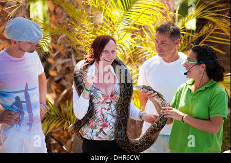 group of tourists holding a snake - Stock Image