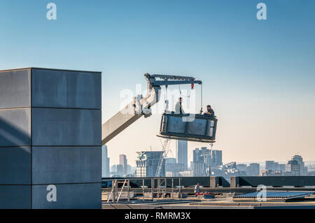 Two workers prepare to descend from the top of a tall building working from an access cradle. City skyline in background. - Stock Image