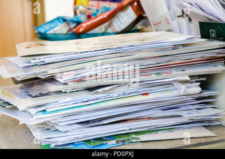 A pile of letters and post sit on a kitchen worktop. - Stock Image