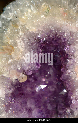 abstract amethyst quartz purple colored, amethyst geode natural crystal gemstone macro shot purple background with bokeh effect - Stock Image