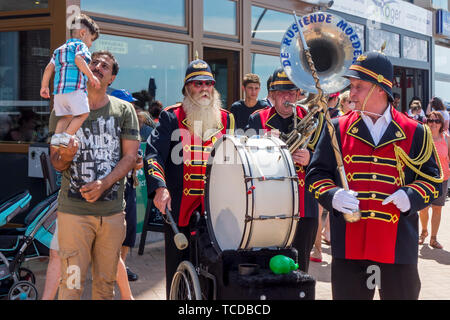 Funny Belgian three man marching band / fanfare band / brass band De Rustende Moeders playing the sousaphone and bass drum on the street in Belgium - Stock Image