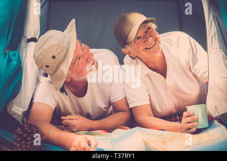 Senior old alternative traveler couple inside a tiny house tent enjoy the travel and the free vacation with camping style - concept of adventure and h - Stock Image