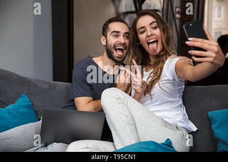 Beautiful young couple relaxing on a couch at home, using laptop computer, taking a selfie - Stock Image