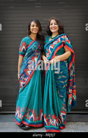 Two Indian women in identical saris at the India Day Parade in Manhattan, New York City. - Stock Image