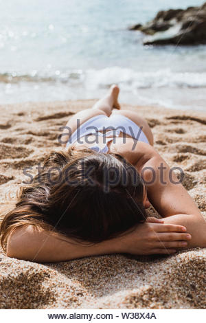 Girl laying face down on the beach - Stock Image