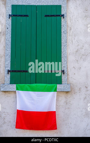 Italian national flag hanging from a closed green  window shutters. - Stock Image