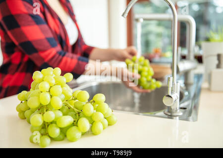 Green grapes on the first plan and a woman rinses  the green grapes with water in the kitchen. - Stock Image